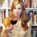 Liz Thach with wine glass and books